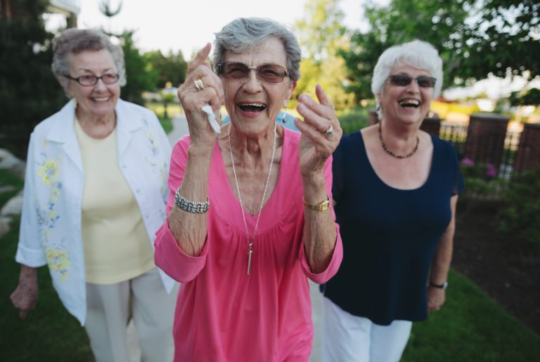 Group of happy caucasian seniors walking and talking outside gar