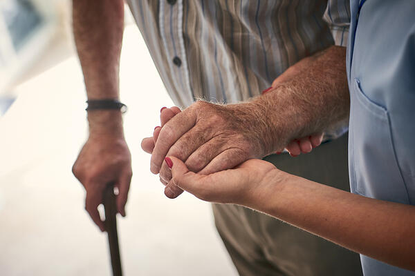 Woman helping a man in long term senior care