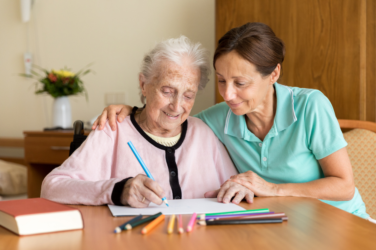 health-aide-sitting-with-elderly-woman-and-helping-with-drawing-exercise-using-colored-pencils